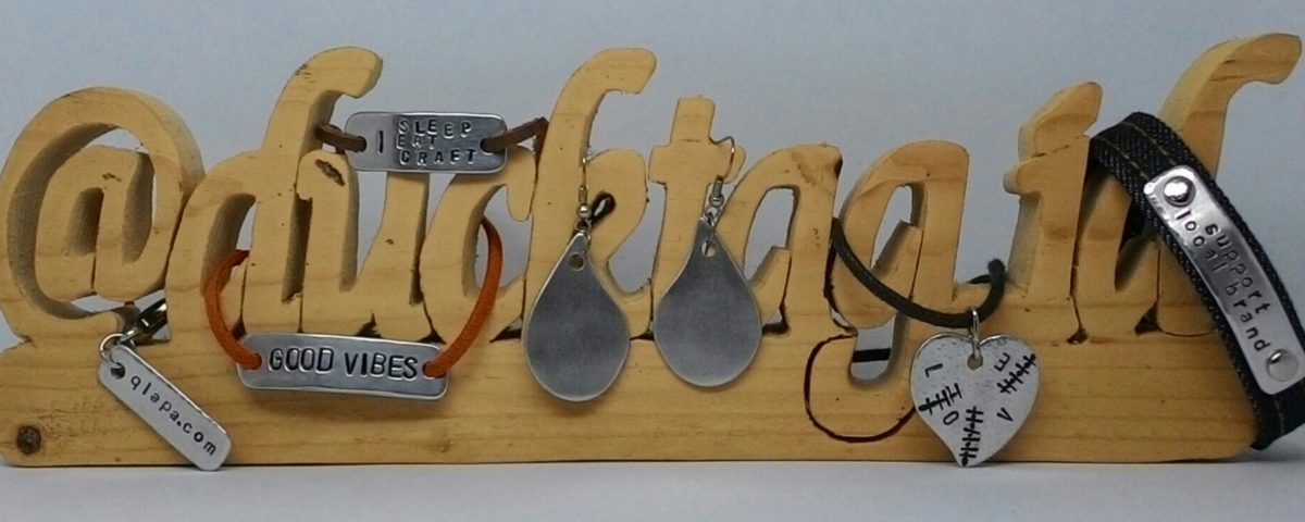 custom handcrafted jewelry displayed on wooden letters